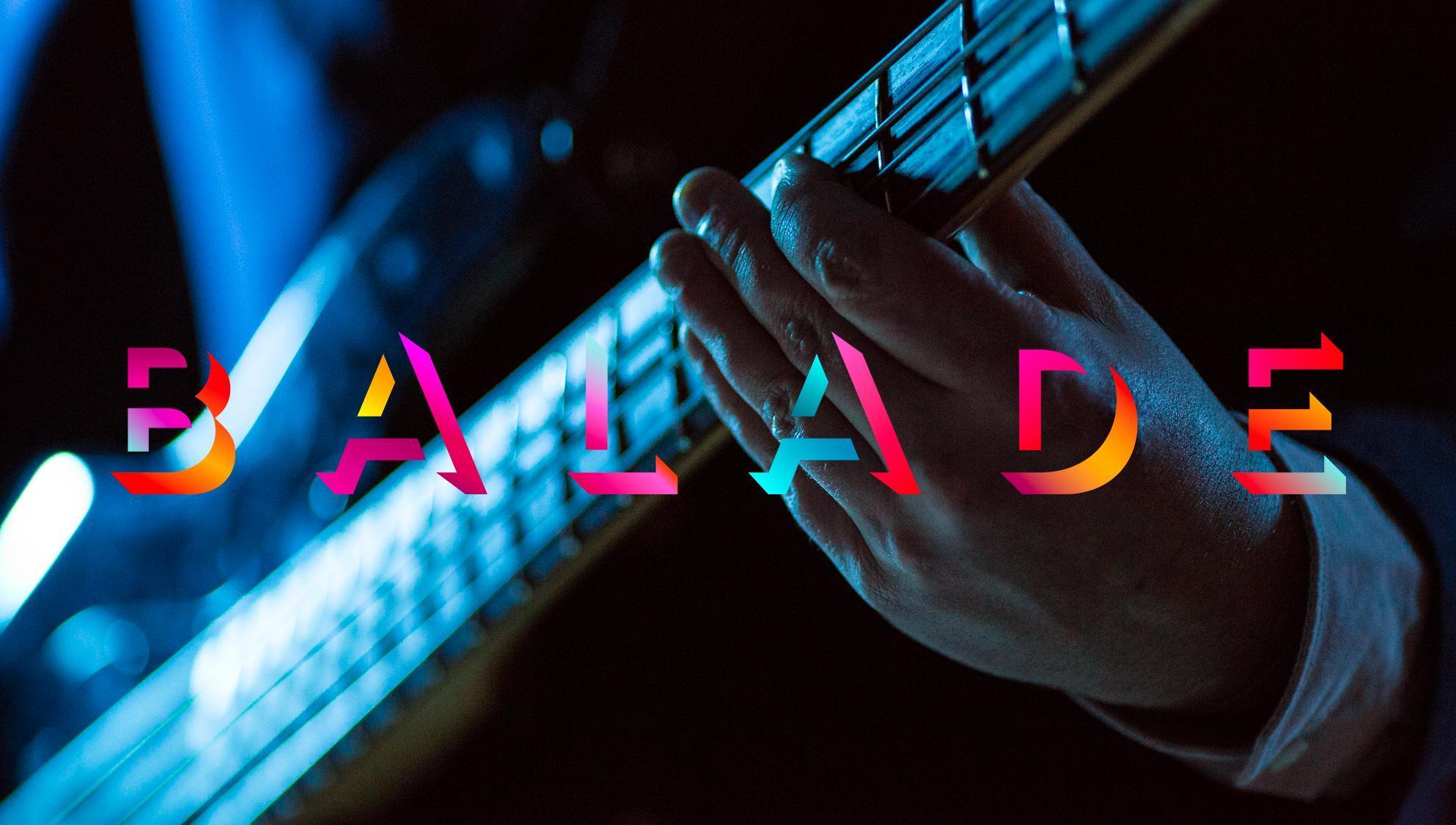Une main tient une guitare.