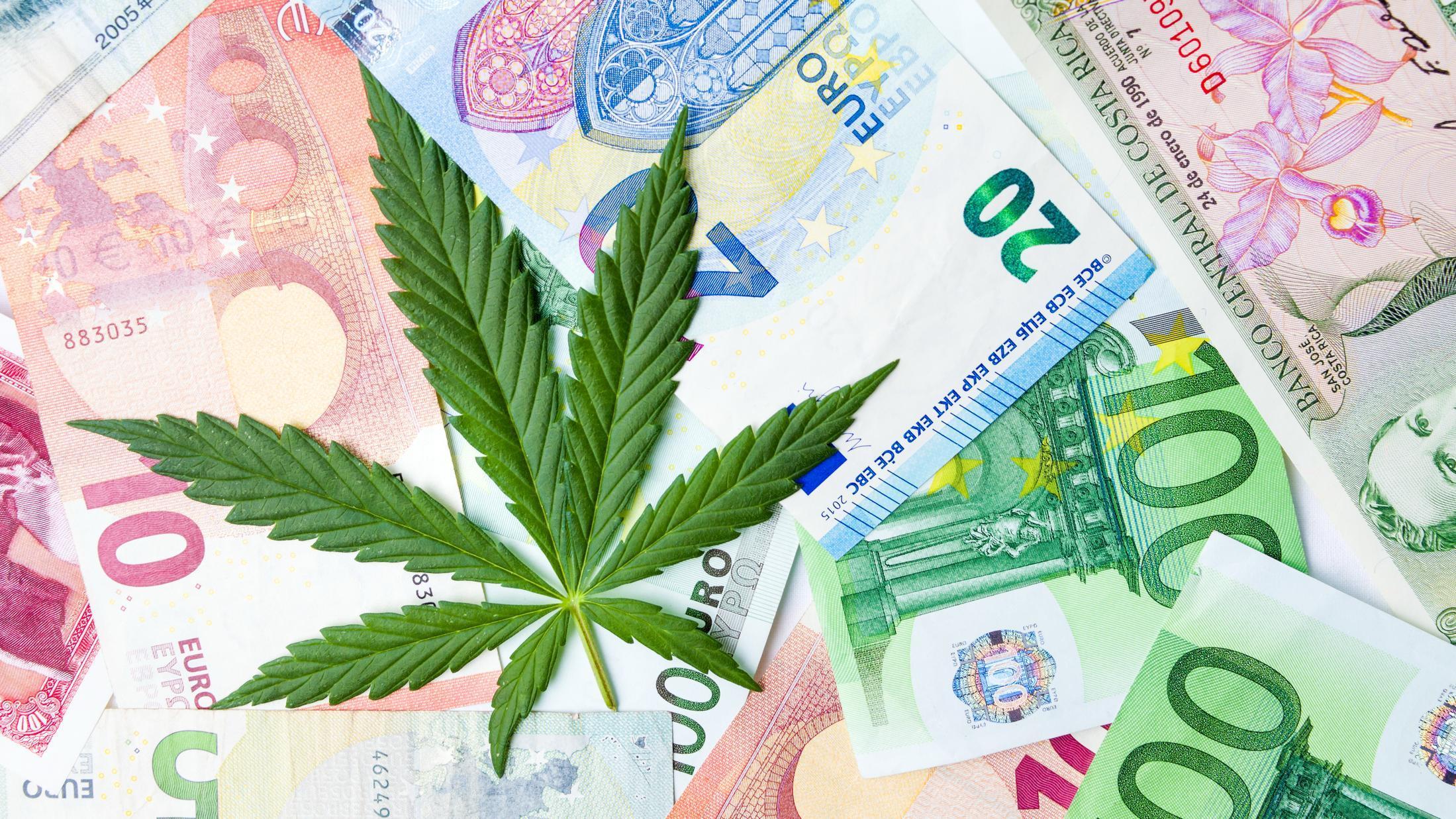 Une feuille de cannabis et de l'argent papier